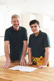 Carpenter And Apprentice Installing Luxury Fitted Kitchen Stock Image