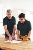 Carpenter And Apprentice Installing Luxury Fitted Kitchen Royalty Free Stock Photos
