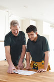 Carpenter And Apprentice Installing Luxury Fitted Kitchen royalty free stock images