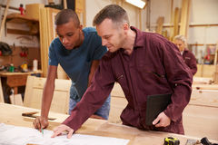 Carpenter With Apprentice Looking At Plans In Workshop Royalty Free Stock Images