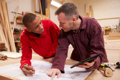 Carpenter With Apprentice Looking At Plans In Workshop Royalty Free Stock Photos
