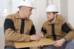 Carpenter apprentice measurement plank. Carpenter apprentice measurement a plank Stock Photography