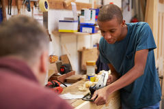 Carpenter With Apprentice Planing Wood In Workshop Stock Photography