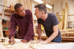Carpenter With Apprentice Planing Wood In Workshop stock photo