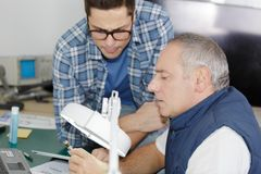 Carpenter with apprentice in training period royalty free stock photography