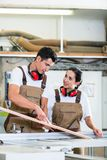 Carpenter and apprentice working together in workshop Royalty Free Stock Photography