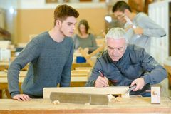 Carpenter and apprentice in workshop royalty free stock image
