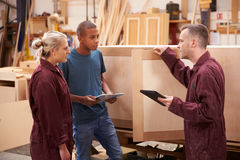 Carpenter With Apprentices Building Furniture In Workshop Royalty Free Stock Photography