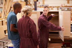 Carpenter With Apprentices Building Furniture In Workshop Royalty Free Stock Image