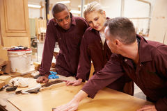 Carpenter With Apprentices Finishing Wood In Workshop Royalty Free Stock Images