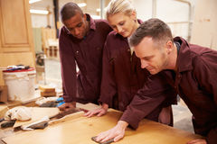 Carpenter With Apprentices Finishing Wood In Workshop Royalty Free Stock Photo