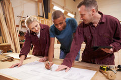 Carpenter With Apprentices Looking At Plans In Workshop Royalty Free Stock Image