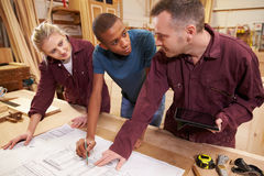 Carpenter With Apprentices Looking At Plans In Workshop Stock Images