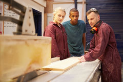 Carpenter With Apprentices Using Circular Saw In Workshop Stock Image