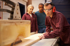 Carpenter With Apprentices Using Circular Saw In Workshop Stock Photography