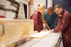 Carpenter With Apprentices Using Circular Saw In Workshop Royalty Free Stock Photo