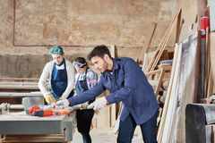 Carpenter in apprenticeship at carpentry shop. During measuring lesson royalty free stock photo