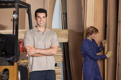 Carpenter With Arms Crossed In Workshop Stock Photo