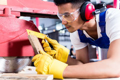 Carpenter in Asian workshop with circular saw Stock Photos