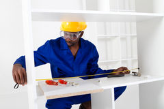 Carpenter assembling furniture. An african american carpenter assembling furniture on white background Royalty Free Stock Photos