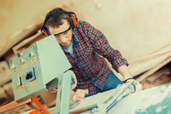 Carpenter with automatic circular saw. He has protective glasses royalty free stock image