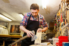 Carpenter with ax and board working at workshop Royalty Free Stock Photo