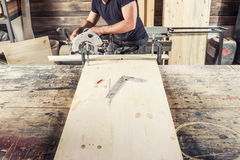Carpenter with a beard and safety glasses. A young male carpenter with a beard and safety glasses saws with a circular saw a wooden board in the workshop Royalty Free Stock Photography