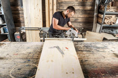 Carpenter with a beard and safety glasses. A young male carpenter with a beard and safety glasses saws with a circular saw a wooden board in the workshop Royalty Free Stock Images