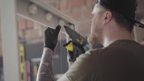The carpenter in black cap and gloves with tattoos on arms putting glue on the wooden frame for the mirror. The worker. The carpenter in black cap and gloves stock video