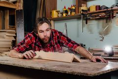 Carpenter blows off wood dust cloud. Carpenter blows off wood dust cloud by wooden billet. Adult man joiner, red checkered shirt, jeans. workshop on the Royalty Free Stock Photography