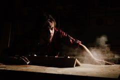 Carpenter blows off wood dust cloud. Carpenter blows off wood dust cloud by wooden billet. Adult man joiner, red checkered shirt, jeans. dark background Stock Photos
