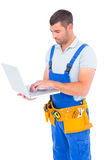 Carpenter in blue overalls using laptop Stock Photo