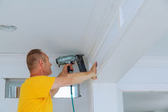 Carpenter brad using nail gun to Crown Moulding framing trim, with the warning label that all power tools Stock Photos