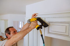 Carpenter brad using nail gun to Crown Moulding on kitchen cabinets framing trim,. With the warning label that all power tools have on them shown illustrating Royalty Free Stock Photo