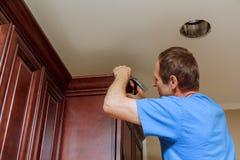 Carpenter brad using nail gun to Crown Moulding on kitchen cabinets framing trim, Stock Images