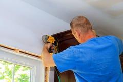 Carpenter brad using nail gun to Crown Moulding on kitchen cabinets framing trim Royalty Free Stock Image