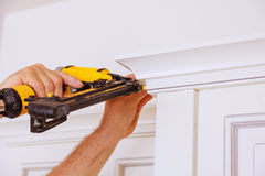 Free Carpenter Brad Using Nail Gun To Crown Moulding On Kitchen Cabinets Framing Trim, Royalty Free Stock Photography - 95619017