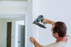 Carpenter brad using nail gun to moldings on doors, that all power tools have on them shown illustrating safety concept Royalty Free Stock Images