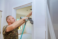 Carpenter brad using nail gun to moldings on doors, Royalty Free Stock Image