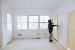 Carpenter brad using nail gun to moldings on doors, framing trim, Royalty Free Stock Photography