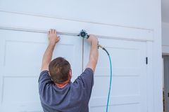Carpenter brad using nail gun to moldings on doors, framing trim, with the warning label that all power tools Royalty Free Stock Photo