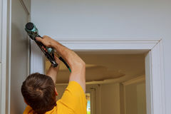 Carpenter brad using nail gun to moldings on doors, framing trim, Royalty Free Stock Image