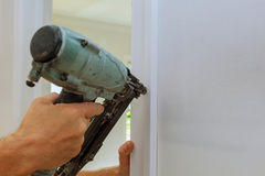 Carpenter brad using nail gun to moldings on doors, Stock Photography
