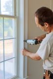Carpenter brad using nail gun to moldings on windows, framing trim, Stock Photography