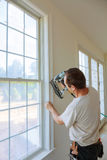 Carpenter brad using nail gun to moldings on windows, framing trim, Stock Photos