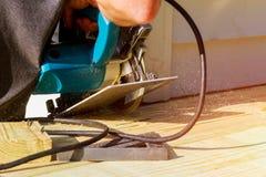 Carpenter building cutting electric circular saw wooden deck. stock photos