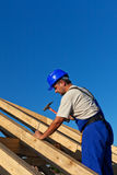 Carpenter building roof structure. Driving in large nail Royalty Free Stock Image