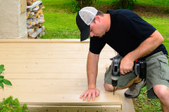 Carpenter Bulding Deck with Drill. A Carpenter in plain black shirt and hat Bulding a Deck and using a drill Stock Photography