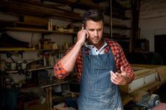 Carpenter calling someone Stock Image