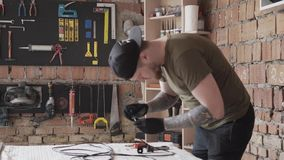 Carpenter in cap working with electrical wires. To much tools for furniture manufacture. Carpenter in cap working with electrical wires. To much tools for stock footage